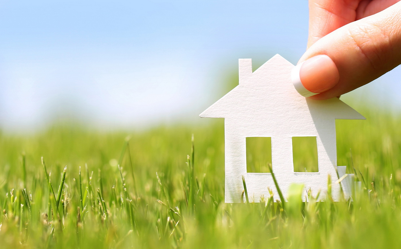 Paper house in green grass over blue sky. Mortgage concept